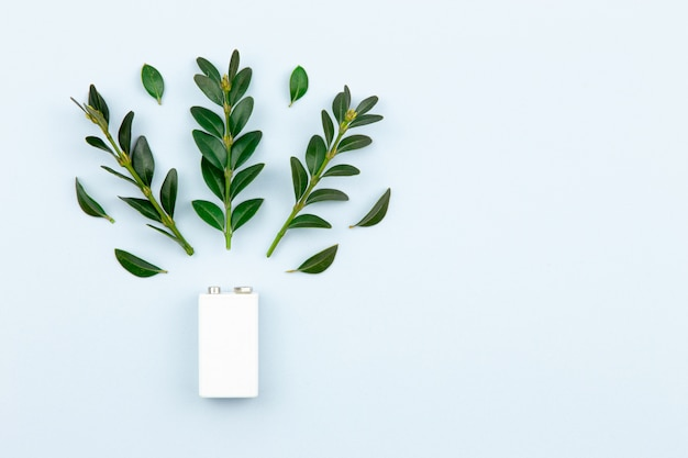 Eco energy or green power illustration with a white battery and sprigs leaves on a light background with copy space for text.