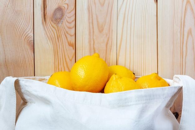 木製の壁のクローズアップの近くに新鮮な丸ごとレモンでいっぱいのエコファイバーバッグ