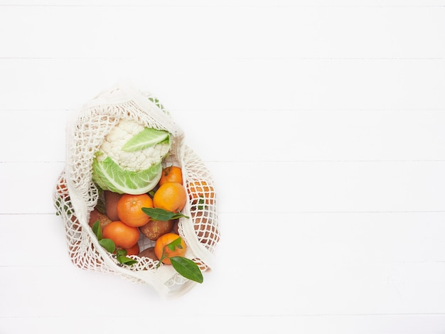 Eco fiendly reusable mesh bag filled with fruits and vegetables, mandarins and cauliflower on white wooden background.