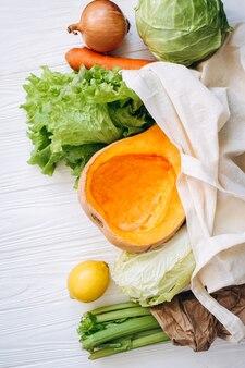 野菜、野菜のエコフラットレイ、布バッグに紙で包まれています。レタス、キャベツ、セロリ、にんじん、かぼちゃ、レモン、バジル。ゼロウェイスト、プラスチックフリーの環境にやさしいコンセプト。