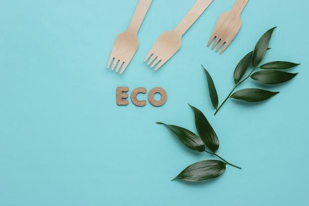 Концепция эко питания деревянные вилки зеленые листья на синем пастельном фоне вид сверху