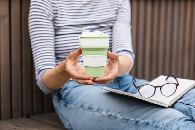 環境にやさしい若い自信のあるヨーロッパの女性は、本を読んだり、コーヒーを飲んだりして休んでいます。