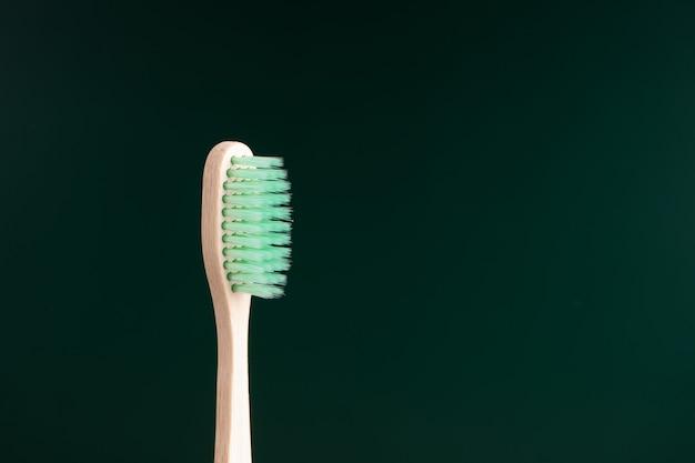 Экологичная антибактериальная зубная щетка из бамбукового дерева на темно-зеленом фоне.