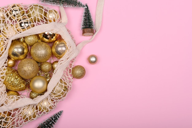 Eco-friendly bag with golden christmas balls and christmas tree on a pink background