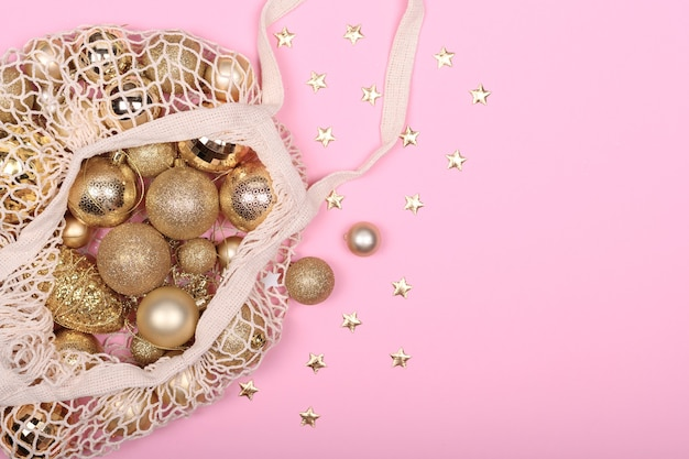 Eco-friendly bag with golden christmas balls on a pink background, zero waist ny.