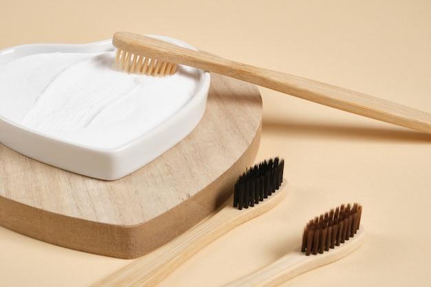Экологичная бамбуковая зубная щетка. бамбуковые зубные щетки и пищевая сода на бежевом фоне, концепция образа жизни с нулевыми отходами. чистить зубы содой
