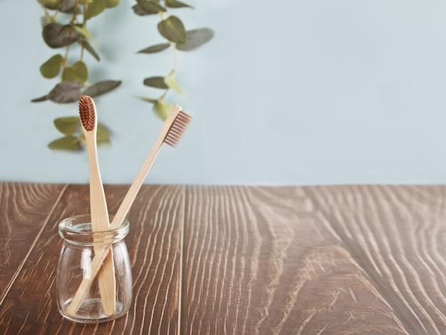 Экологичные бамбуковые зубные щетки на деревянном столе в стакане. нулевые отходы.