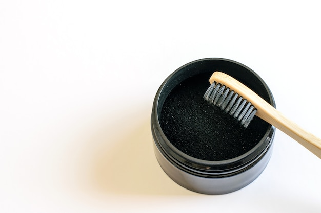 Eco-friendly bamboo toothbrush and activated charcoal powder for teeth whitening.