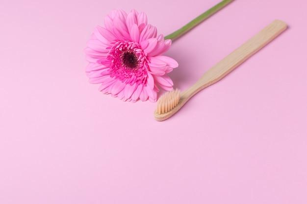 Экологичная бамбуковая зубная щетка и цветок на розовом фоне