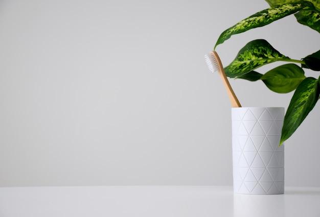 Экологичная бамбуковая зубная щетка в белом держателе и зеленые листья на белом фоне