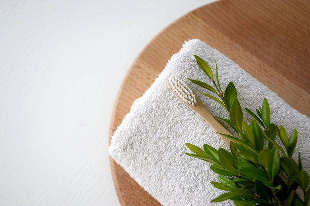 Eco friendly bamboo toothbrush on white towel and green leaf on wooden round board