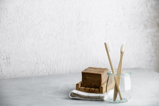 Eco-friendly bamboo toothbrushes in a glass jar and handmade organic soap, copy space
