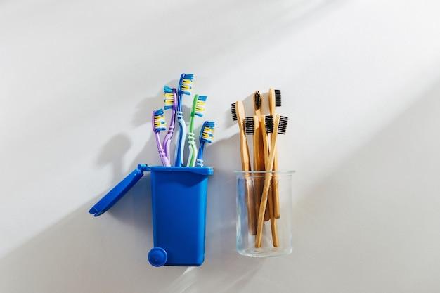 유리에 담긴 친환경 대나무 칫솔과 쓰레기통에 플라스틱 칫솔.