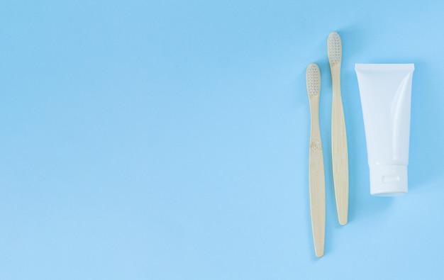 ライトブルーの歯磨き粉の横にある環境に優しい竹の歯ブラシ