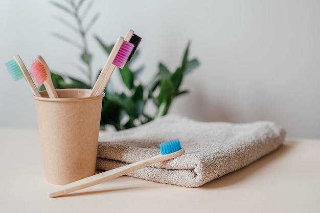 紙コップ、ゼロウェイストコンセプト、持続可能なライフスタイルのさまざまな色の環境に優しい竹の歯ブラシ