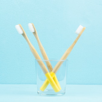 Eco-friendly bamboo toothbrushes in a transparent glass on a blue background