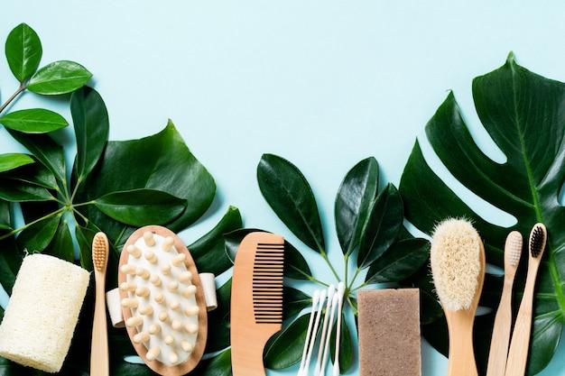 エコフレンドリーなバスルームアクセサリーやスパツールは、青い背景にモンステラの葉を残します。化粧品コンクリートの背景。美しさとゼロウェイストのコンセプト。