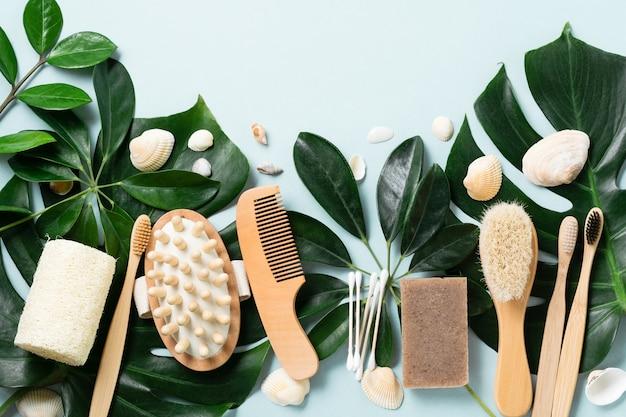Экологичные аксессуары для ванной комнаты или спа-инструменты на листьях монстера на синем фоне. косметический конкретный фон. концепция красоты и нулевых отходов.