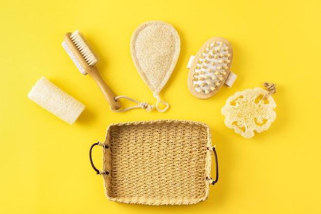 Экологичные аксессуары для ванных комнат. многоразовые предметы для ванны из эко материала, антицеллюлитный массажер, губка из люфы на желтом.