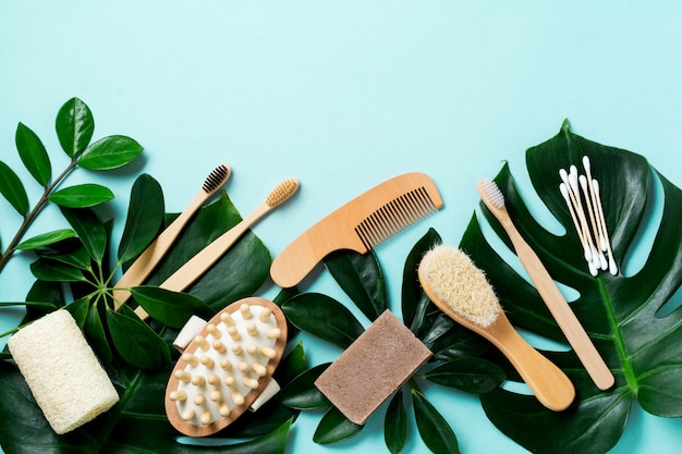 Eco friendly bathroom accessories or spa tools on leaves monstera on blue background. cosmetic concrete background. beauty and zero waste concept.