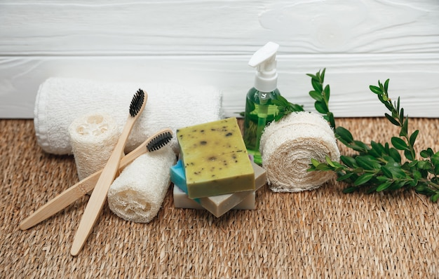 Eco friendly bathroom and hygiene accessories. bamboo toothbrushes, white towel, luffa sponge, handmade organic soap with green plant. beauty, spa treatment concept.