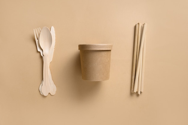 環境にやさしい生分解性の使い捨てカップと個々のスプーン、フォーク、ベージュのスペースの竹ストロー