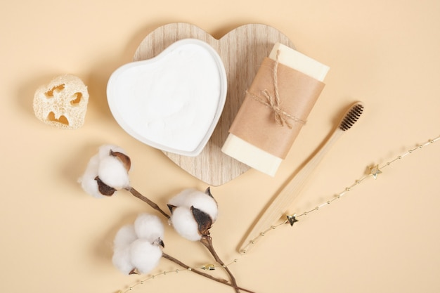 Eco friendly body care set, soap, soda, loofah and cotton flower on beige background, bamboo toothbrush. zero waste lifestyle concept, natural cosmetics top view copy space