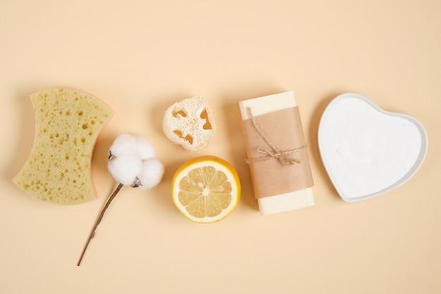 環境にやさしいクリーニングとボディケアキット、レモン、石鹸、ソーダ、ヘチマ、スポンジ、ベージュの背景に綿の花、ゼロウェイストライフスタイルコンセプトトップビューコピースペース