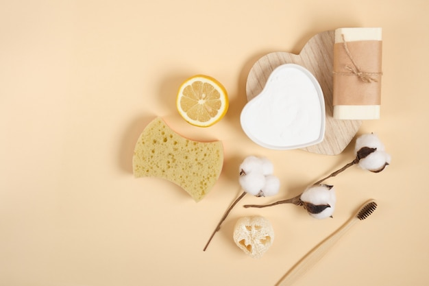 Eco friendly cleaning and body care kit, lemon, soap, soda, loofah, sponge and cotton flower on beige background, zero waste lifestyle concept top view copy space