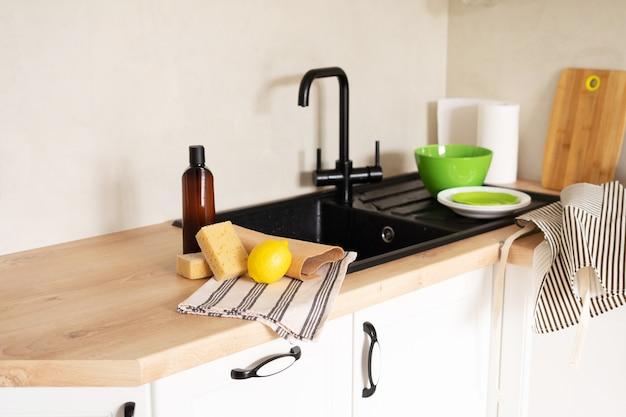 モダンなキッチンにある環境にやさしいクリーニング製品と食器用洗剤。ココナッツスポンジ、重曹、天然洗濯石鹸、レモン。ゼロウェイスト。