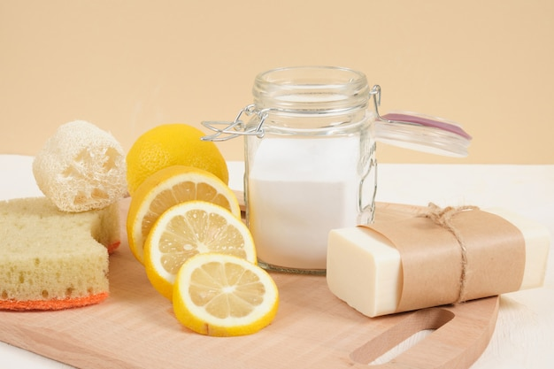 Экологичный набор для чистки, сода и лимон для чистоты, безотходного образа жизни. пищевая сода в стеклянной банке, мыло, люффа и нарезанный лимон на бежевом фоне