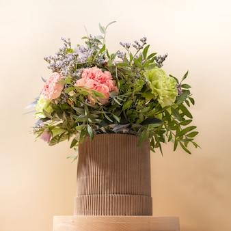 Экологически чистый состав с букетом цветов в картонной вазе diy, стоящей на деревянной круглой подставке на бежевом фоне.