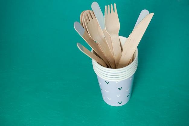 Эко-концепция одноразовая посуда на зеленом столе. деревянные вилки и ложки в бумажном стаканчике сверху