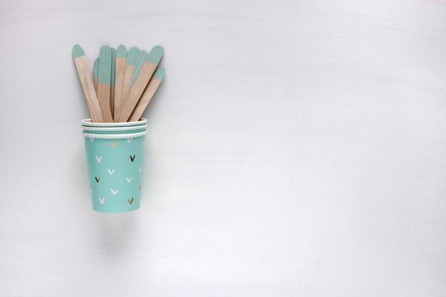 Эко-концепция плоская планировка одноразовой кухонной утвари на сером столе. деревянные вилки и ложки в бумажном стаканчике