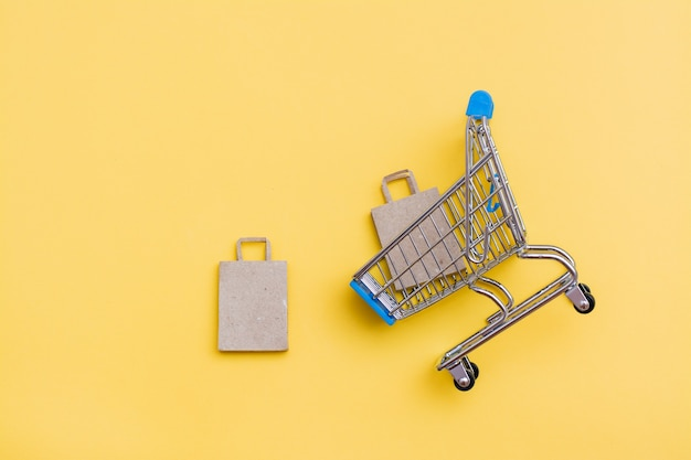Eco-friendly craft paper bag in  a metal shopping cart and near it on a yellow background. black friday, gift sales. top view. copy space