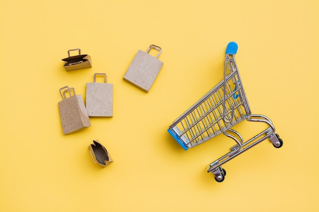 Eco-friendly craft paper bags next to a metal shopping cart on a yellow background. black friday, gift sales. top view