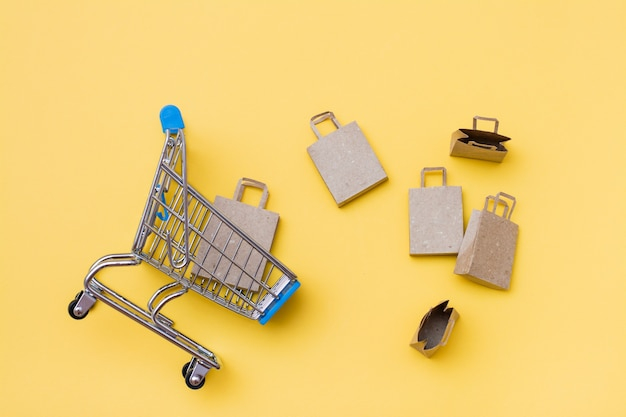 Eco-friendly craft paper bags in and near a metal shopping cart on a yellow background. black friday, gift sales. top view