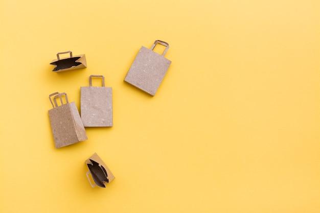 黄色の背景に環境に優しいクラフト紙袋。ブラックフライデー、ギフト販売。上面図。コピースペース