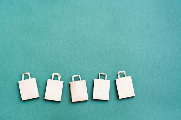 緑の背景に一列に並んだ環境にやさしいクラフト紙の買い物袋。ブラックフライデーギフトの販売。コピースペース