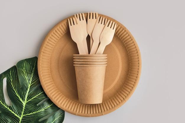 Эко дружелюбная посуда из бумаги ремесла на серой поверхности с листом монстера