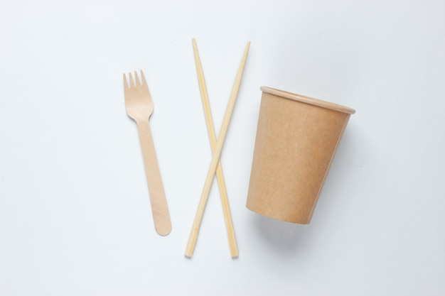 Eco-friendly cutlery. chinese chopsticks, wooden fork, craft paper cup on white background. minimalism eco concept.