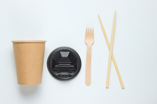 Экологичные столовые приборы. китайские палочки для еды, деревянные вилки, бумажный стаканчик на белом фоне. эко-концепция минимализма.