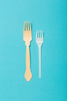 Eco-friendly dishes, wooden and plastic forks on a blue background