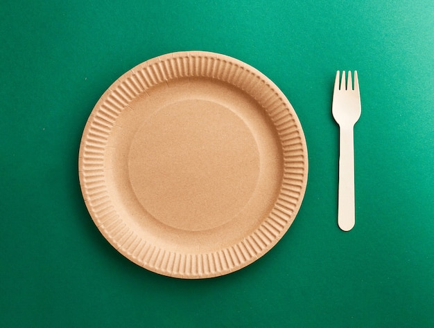 Eco friendly disposable dishes on green background. sustainable lifestyle concept. zero waste, plastic free, stop plastic pollution.