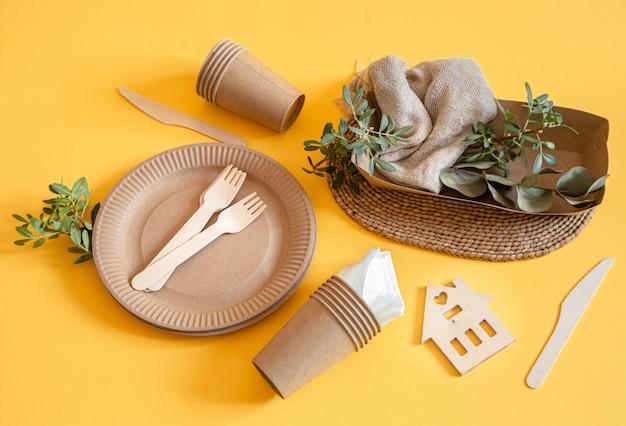 Экологичная одноразовая посуда из бумаги на оранжевой поверхности