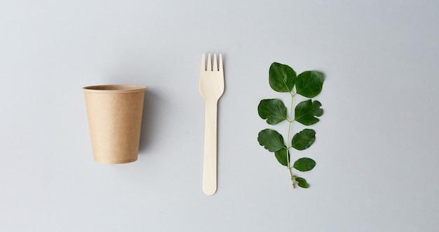 灰色の背景に環境に優しい使い捨て食器。持続可能なライフスタイルのコンセプト。ゼロウェイスト、プラスチックフリー、プラスチック汚染を防ぎます。