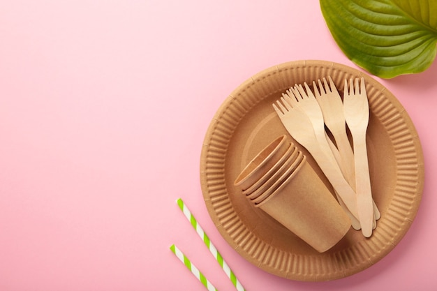 ピンクの背景に緑の葉を持つ環境に優しい使い捨て食器。ゼロウェイスト、環境にやさしい、プラスチックフリーの背景。上面図