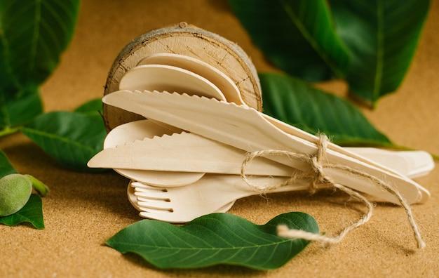 녹색 잎에 친환경 일회용 주방용품이 놓여 있습니다. 플라스틱 거부.