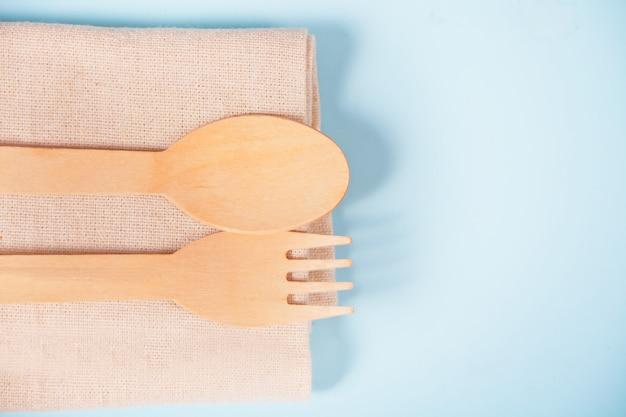 Экологичные одноразовые кухонные принадлежности посуда столовые приборы. деревянная вилка и ложка на хлопковой тряпке. экологическая концепция. ноль отходов. вид сверху. копировать пространство