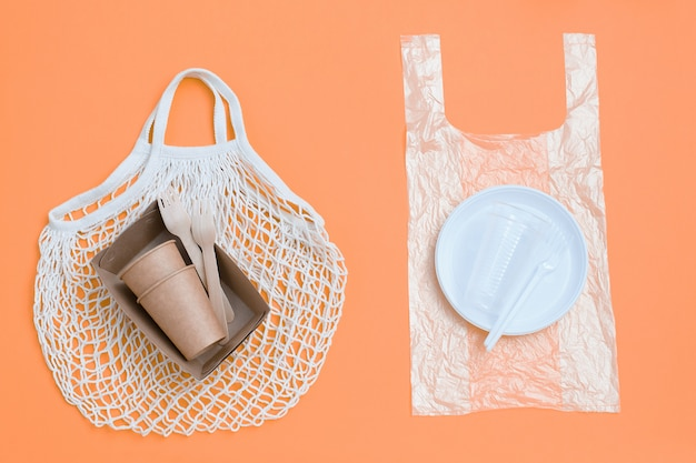 Eco-friendly disposable tableware on eco friendly mesh bag and plastic harmful dishes and cutlery on plastic bag.